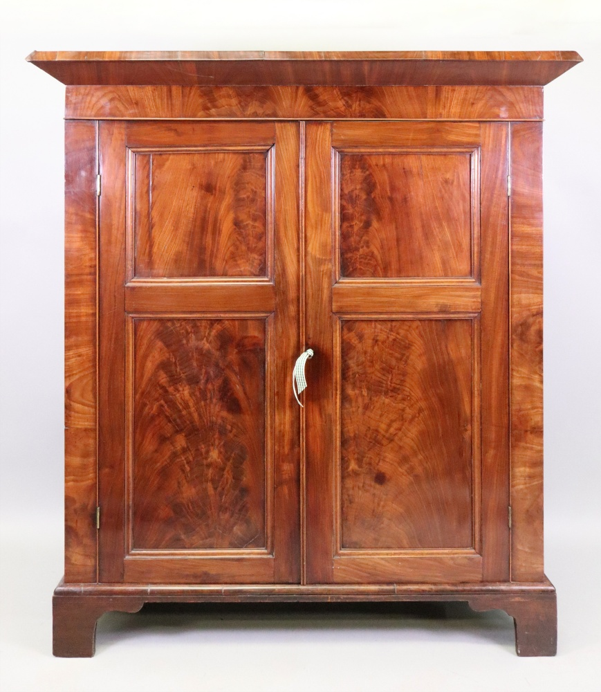 Lot 1322 - A William IV mahogany cabinet, fitted with shelves enclosed by a pair of panelled doors,