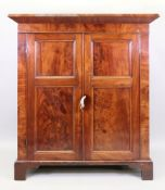 A William IV mahogany cabinet, fitted with shelves enclosed by a pair of panelled doors,