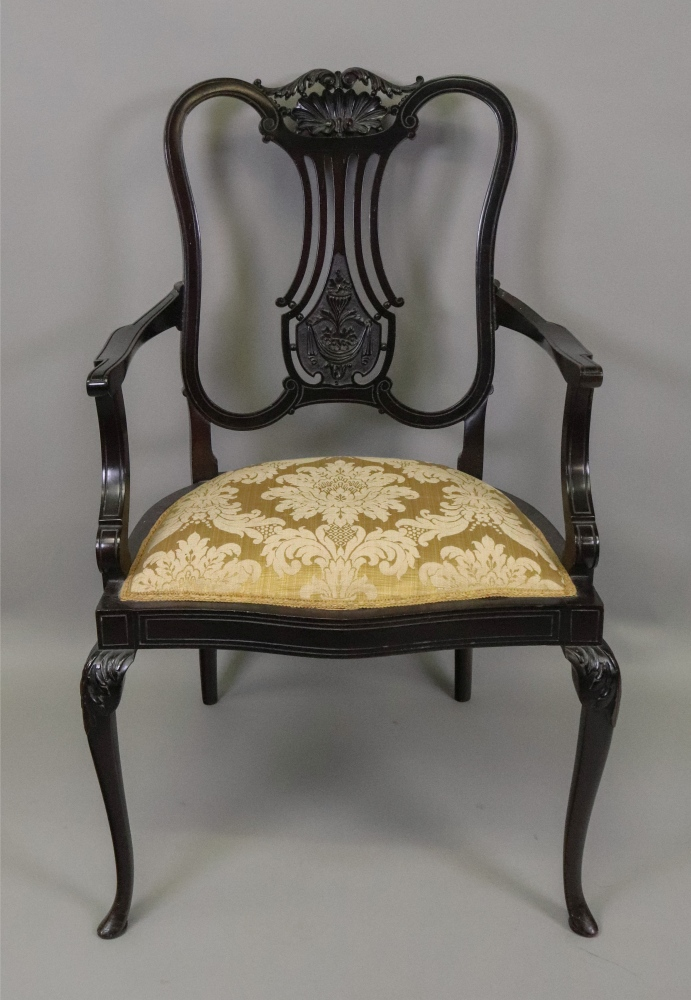 Lot 1349 - An Edwardian 'Chippendale Revival' dark stained foliate carved mahogany salon elbow chair.