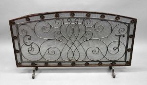 A large arched top rectangular wrought iron and mesh fireguard, 128cm wide x 72cm high.