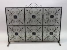 A large rectangular wrought iron and mesh fire guard, 115cm wide x 90cm high.