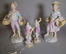 A pair of continental Meissen-style porcelain figures of boy and girl carrying baskets,