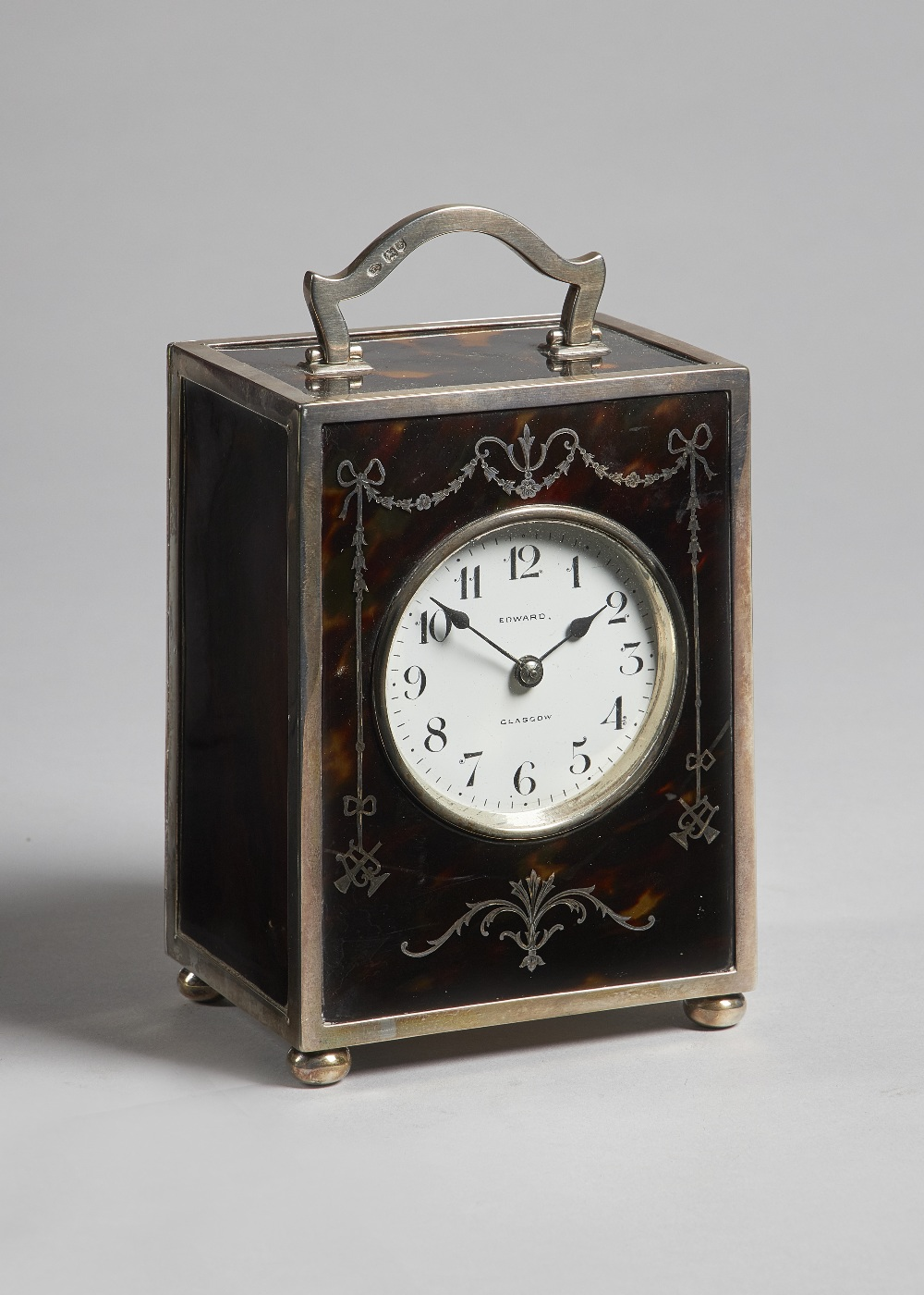 Lot 685 - An Edwardian silver and tortoiseshell carriage clock London 1909 The rectangular case with a shaped