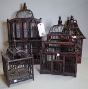 A group of four 20th century black lacquer and hardwood bird cages of various forms, the largest,