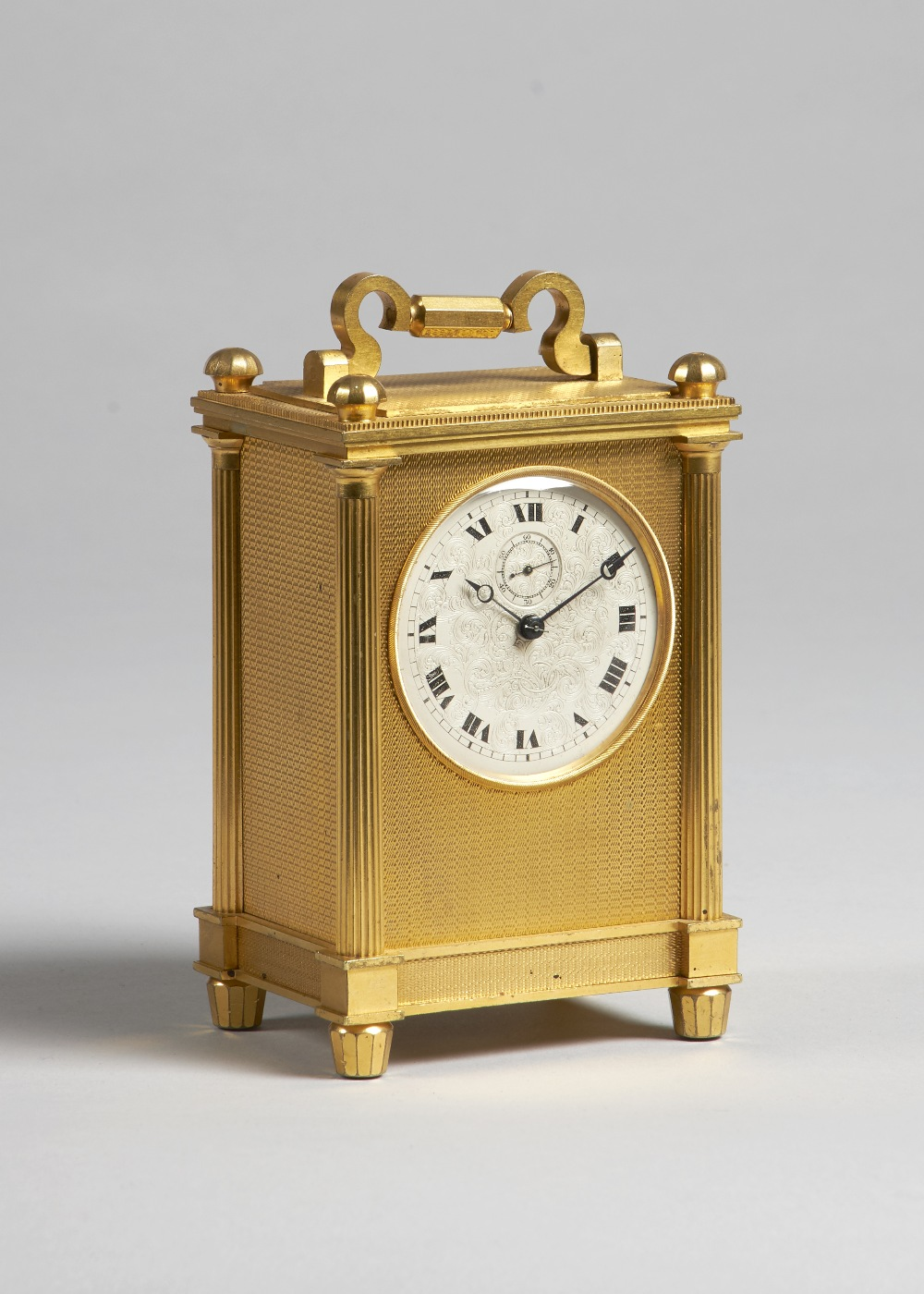 Lot 693 - An English giltmetal carriage timepiece Circa 1870 The rectangular case with shaped handle and