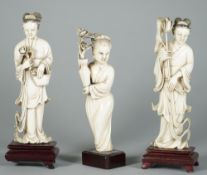 A pair of Chinese ivory figures of young women, early 20th century, each standing in long robes,