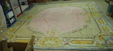 A Savonnerie carpet, French, the plain pale pink field with trellis spandrels and floral garlands,