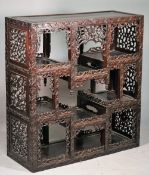 A 19th century Chinese hardwood side cabinet with eleven recesses,
