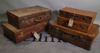 A group of five early 20th century leather bound suitcases, the largest 66cm wide x 18cm high, (5).