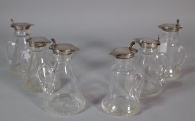 A matched set of six glass and silver topped small jugs, (6).