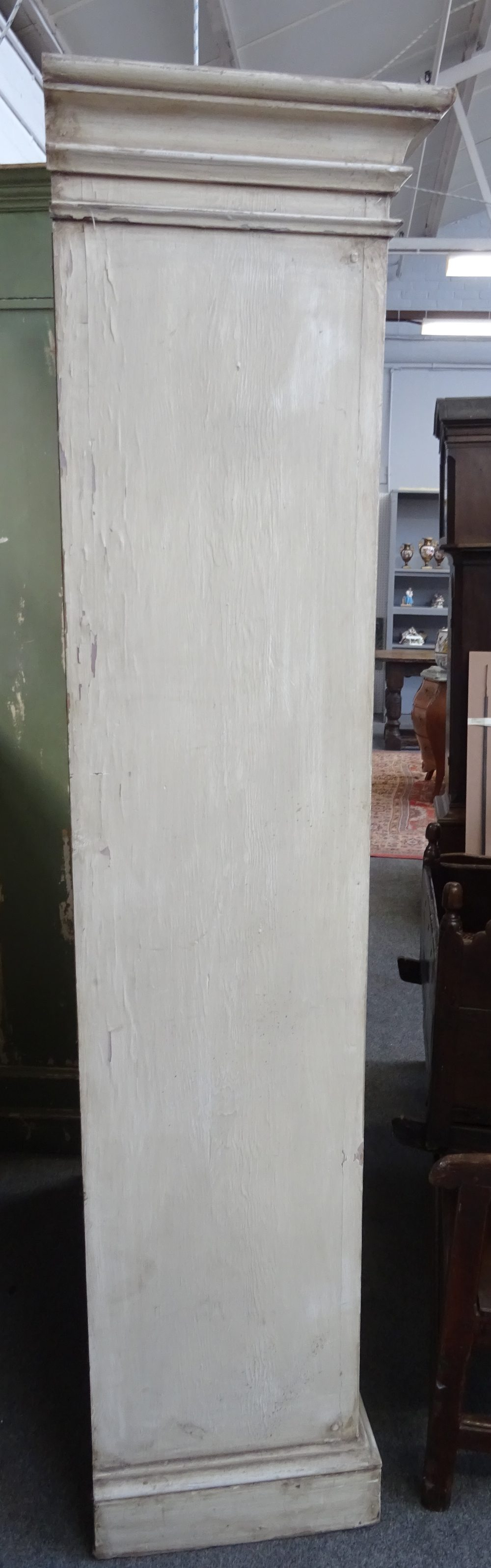 Lot 1827 - A pair of distressed white painted floor standing breakfront open bookcases, each on plinth base,