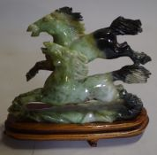 A 20th century Chinese hardstone figure of two horses on a hardwood stand.