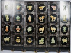 A mid-20th century Eastern black lacquer six fold screen, relief decorated with soapstone vessels,