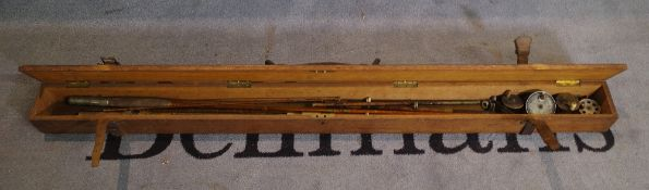An early 20th century fishing rod box, 138cm long, containing split cane rods and reels.