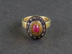 A silver gilt, cabochon ruby and diamond set dress ring of oval plaque design,