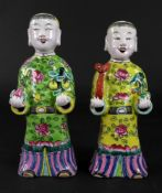 A pair of Chinese famille rose figures of boys, late 19th/20th century,