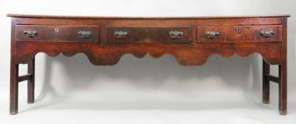 A George III oak low dresser, of narrow proportions,