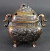 A Chinese or Japanese bronze two handled censer and cover, circa 1900, of rounded square form,