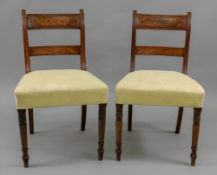 A pair of Regency mahogany ebony banded dining chairs, with curved panelled top rails and bar backs,