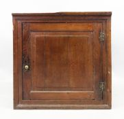 An 18th century oak cupboard, of narrow proportions, with a moulded cornice,