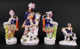 A pair of Victorian Staffordshire pottery highland figures, each with a pet lamb, 23.