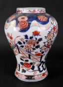 A Japanese Imari baluster vase, Meiji period, painted with flowering shrubs in a fenced garden,