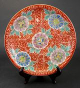 A Japanese Imari plate, Meiji period, painted with five flowers against an iron red ground,