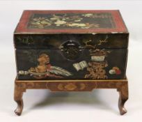 A Chinese lacquered trunk, gilt and painted on a black ground, with side carrying handles,