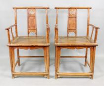 A pair of Chinese open arm elbow chairs, with carved and pierced and panelled splats,