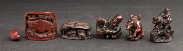 A group of six wooden netsuke to include; a figure riding a cow crossing a bridge, a reading lesson,