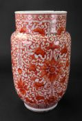 A Chinese porcelain vase, 19th century, of cylindrical form, painted in iron-red with lotus flowers,