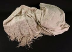 A large ivory silk shawl, late 19th century, embroidered all-over with flowers within a deep fringe,