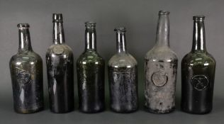 A collection of six old green glass wine and spirits bottles,