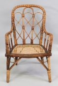 A child's Victorian rattan open arm elbow chair, circa 1890, with arched back,