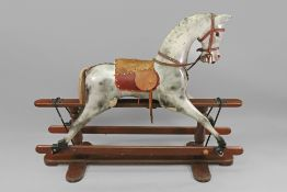 A child's dappled wooden rocking horse, second half 20th century, with leather saddle and reins,