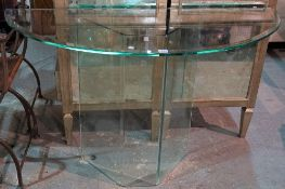 A modern demi-lune glass console table, on a glass base, 120cm wide x 75cm high.