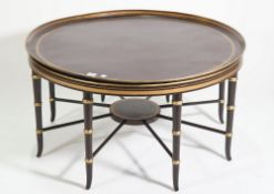 A modern ebonised and parcel gilt decorated circular metal tray on a wooden base,