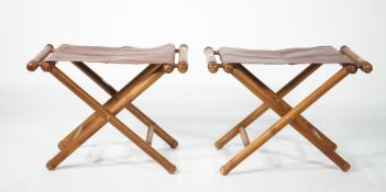 A pair of modern stained beech and leather folding 'X' frame stools, 63cm wide x 46cm high, (2).