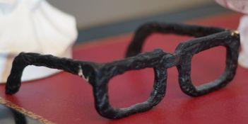 A pair of bronze glasses, a bronze model of a fountain pen and a bronze grass hopper (3).