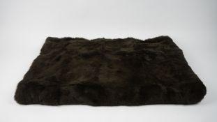 A dark brown fur throw, 180cm x 124cm.