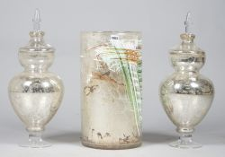 A modern cylindrical glass stick stand, 50cm high and a pair of silvered glass vases, 60cm high, (a.