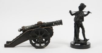 A modern spelter figure of a boy, 31cm high, and a cast metal model of a cannon, (2).