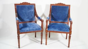 A pair of George III style mahogany framed open armchairs, with blue velvet upholstery,