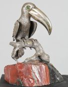 A 20th century silver model of a Toucan with malachite set eyes, resting on a rustic branch,