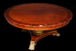 A Regency style mahogany circular low centre table on trefoil base and giltwood claw feet,
