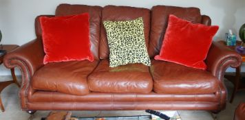 A tan leather upholstered suite, comprising; an armchair, 107cm wide x 100cm high,