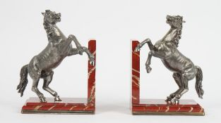A pair of silver plated and red marble bookends, formed as rearing horses, the bases with.