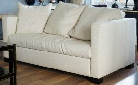 A cream upholstered two seater sofa, 177cm wide x 70cm high.