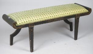 A modern Italian black and parcel gilt painted window seat with rollover arms,