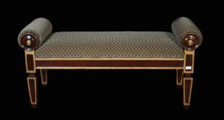 A Regency style mahogany and parcel gilt window seat with rollover arms on tapering square supports,